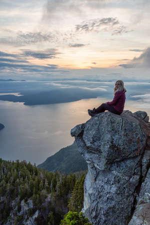 Escursionista femminile avventurosa in cima a una montagna coperta di nuvole durante un vibrante tramonto estivo. Preso sulla sommità del vertice di St Marks, West Vancouver, British Columbia, Canada.