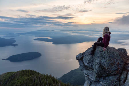 Adventurous Female Hiker on top of a mountain covered in clouds during a vibrant summer sunset. Taken on top of St Marks Summit, West Vancouver, British Columbia, Canada.