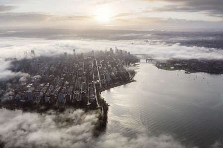 Downtown Vancouver, British Columbia, Canada. Aerial View of a modern city on the West Coast of Pacific Ocean during a cloudy sunrise and covered in Fog.