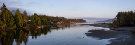 Beautiful Panoramic View of a river joining the ocean in a small town during a cloudy and sunny summer sunrise. Taken at Port Renfrew, Vancouver Island, BC, Canada.