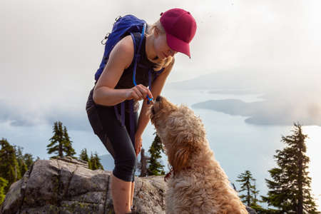 Adventurous Woman Hiker and dog are dinking water during a cloudy and sunny summer day. Taken while hiking on a mountain near Vancouver, British Columbia, Canada.