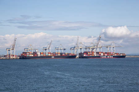 Tsawwasen, Greater Vancouver, BC, Canada - July 14, 2019: Big Container ships are being loaded at the port during a sunny summer day.