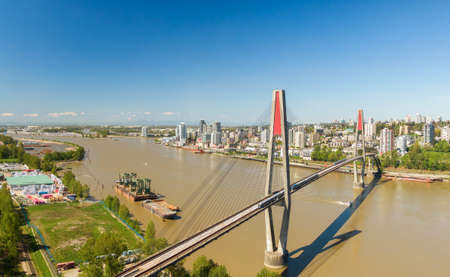 Aerial view of Skytrain Bridge over the Fraser River. Taken in Surrey, Greater Vancouver, British Columbia, Canada.