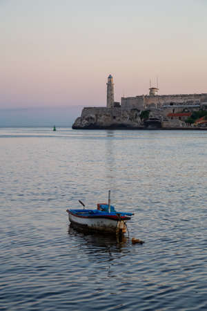 Beautiful view of the small fishing boat with the Lighthouse in the background. Taken in the Old Havana City, Capital of Cuba, during a colorful and sunny sunrise.