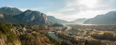 Aerial panoramic view of a small town with Chief Mountain in the background during a sunny day. Taken in Squamish, North of Vancouver, British Columbia, Canada.