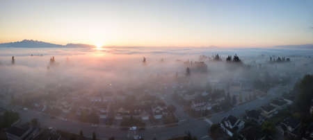Aerial view of a residential neighborhood covered in a layer of fog during a vibrant sunrise. Taken in Greater Vancouver, BC, Canada.
