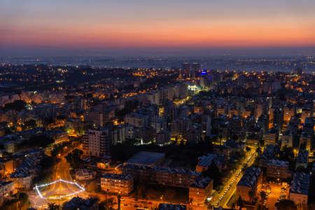 Vista aérea de un barrio residencial en una ciudad durante un amanecer vibrante y colorido. Tomada en Netanya, Distrito Central, Israel.