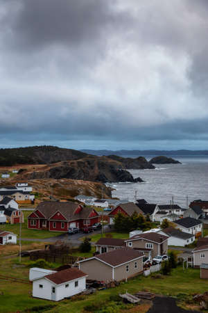 Beautiful view of a small town on the Atlantic Ocean Coast during a cloudy evening. Taken in Crow Head, North Twillingate Island, Newfoundland and Labrador, Canada.