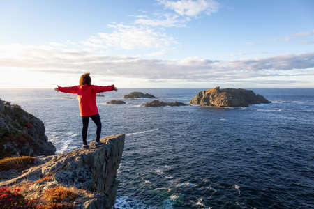 Woman in red jacket is standing at the edge of a cliff with open arms and enjoying the beautiful ocean scenery. Taken in Crow Head, North Twillingate Island, Newfoundland and Labrador, Canada.