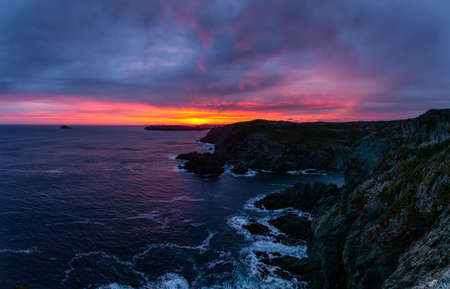 Striking seascape view on a rocky Atlantic Ocean Coast during a colorful sunrise. Taken at Crow Head, North Twillingate Island, Newfoundland and Labrador, Canada.