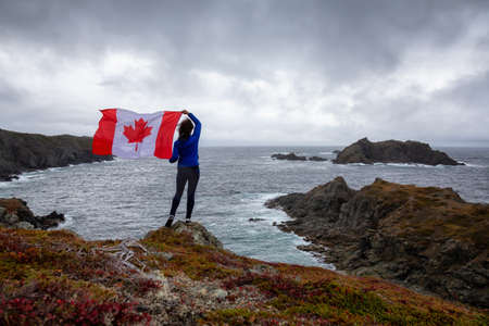 Adventurous woman holding a Canadian Flag on a Rocky Atlantic Ocean Coast during a cloudy day. Taken in Sleepy Cove, Crow Head, Twillingate, Newfoundland, Canada.
