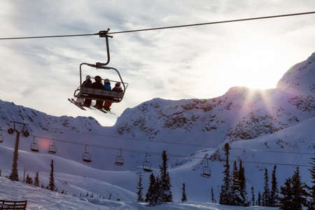Whistler, British Columbia, Canada. People going up the mountain on a Chairlift during a vibrant and sunny winter day.