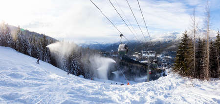 Whistler, British Columbia, Canada. Gondola going up the mountain during a vibrant and sunny winter day.