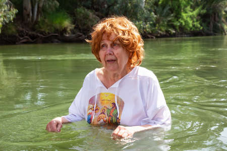 Elder woman is being baptised at Jordan River in the holy land of Israel.