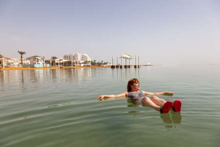 Happy and Joyful Middle Age woman is swimming and relaxing in the Dead Sea during a sunny day. Taken in Ein Bokek, Israel.