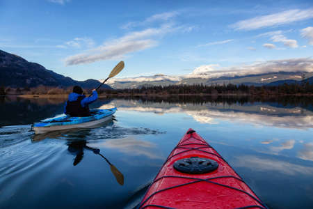 Adventurous man kayaking in peaceful water during a cloudy winter day. Taken in Squamish, North of Vancouver, BC, Canada.
