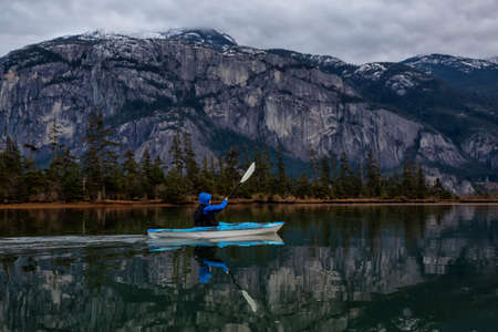 Adventurous man kayaking in peaceful water during a cloudy winter sunset. Taken in Squamish, North of Vancouver, BC, Canada.