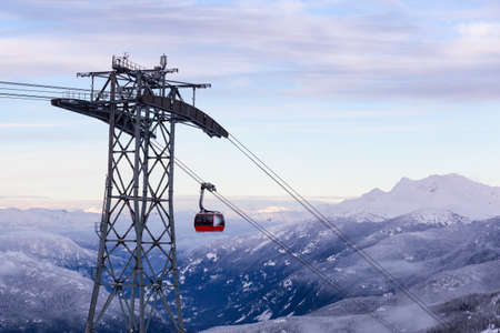 Whistler, British Columbia, Canada. Beautiful View of Peak to Peak Gondola with the Canadian Snow Covered Mountain Landscape during a cloudy and vibrant winter sunset Stock Photo