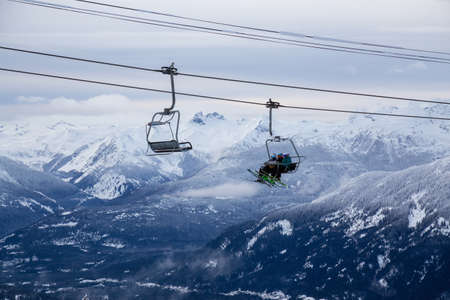Whistler, British Columbia, Canada. People going up the mountain on a Chairlift during a vibrant and cloudy winter day. Stock Photo
