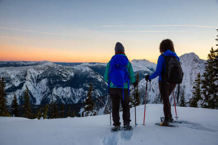Couple friends are snowshoeing on top of a mountain during a vibrant winter sunset. Taken on top of Zoa Peak near Hope, British Columbia, Canada. 版權商用圖片