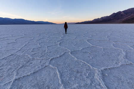 Woman walking on Salt Pan at the Badwater Basin, Death Valley National Park, California, United States.