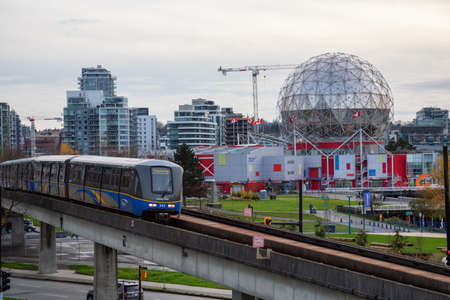 Downtown Vancouver, British Columbia, Canada - November 29, 2018: Skytrain passing in the modern city during a cloudy evening.