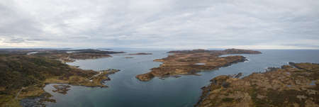 Aerial panoramic view of a small town on a rocky Atlantic Ocean Coast during a cloudy day. Taken in Quirpon, Newfoundland, Canada. Archivio Fotografico