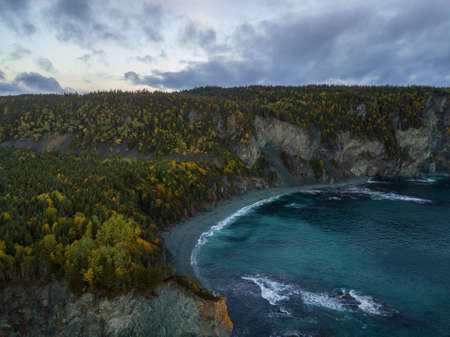 Aerial Canadian Landscape View by the Atlantic Ocean Coast during a cloudy sunrise. Taken in Beachside, Newfoundland, Canada.