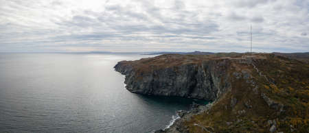 Aerial panoramic view of a rocky Atlantic Ocean Coast during a cloudy day. Taken in St. Anthony, Newfoundland, Canada.