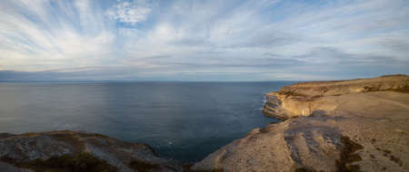 Aerial panoramic view of a rocky Atlantic Ocean Coast during a cloudy sunset. Taken in Burnt Cape Ecological Reserve, Raleigh, Newfoundland, Canada.