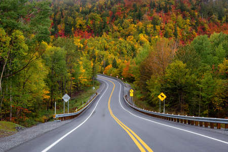 Scenic road in the mountains surrounded by vibrant Fall Color Trees. Taken in Forillon National Park, near Gaspe, Quebec, Canada.