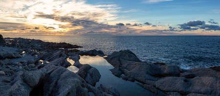 Beautiful rocky Atlantic Ocean Coast during a vibrant sunset. Taken at Cow Head, Newfoundland, Canada.