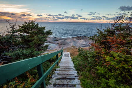 Wooden stairs going down to a beautiful rocky Atlantic Ocean Coast during a vibrant sunset. Taken at Cow Head, Newfoundland, Canada. Archivio Fotografico