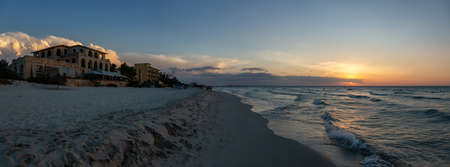 Beautiful panoramic view of vacation resort on the sandy beach during a dramatic cloudy sunset. Taken in Varadero, Cuba.