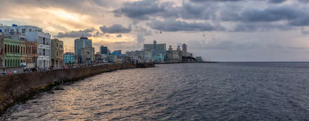 Panoramic view of the Old Havana City, Capital of Cuba, by the ocean coast during a dramatic cloudy sunset.