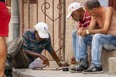 Havana, Cuba - May 16, 2019: Men playing board game on the sidewalk in the Old Havana City during a vibrant and bright sunny day.