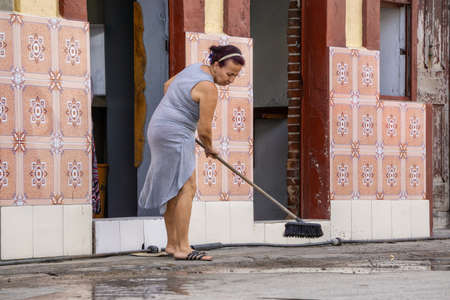 Havana, Cuba - May 16, 2019: Woman cleaning the streets by the entrance of her home in the Old Havana City during a vibrant and bright sunny day.
