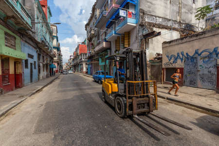 Havana, Cuba - May 14, 2019: Man driving a Forklift in the streets of the Old Havana City during a vibrant and bright sunny day. Editorial