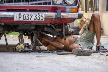 Havana, Cuba - May 17, 2019: Dirty Cuban Car Mechanic is working underneath the vehicle in the streets of Old Havana City during a hot sunny day.