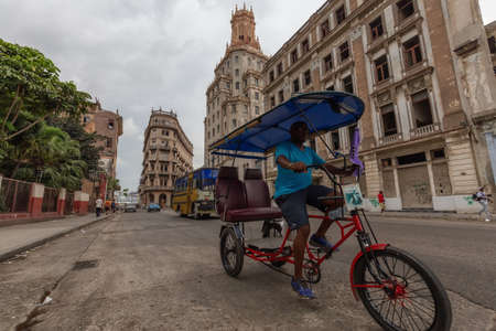 Havana, Cuba - May 14, 2019: Bicycle Taxi Driver riding in the streets of Old Havana City during a cloudy day.