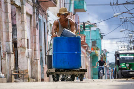 Havana, Cuba - May 17, 2019: Old man pushing a container full of water in the streets of Old Havana City during a hot sunny day.