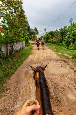 Trinidad, Cuba. Horseback Riding on a dirty trail in the country side near a small Cuban Town during a vibrant sunny day. Banco de Imagens