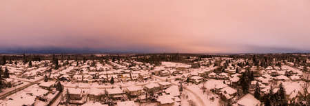 Aerial Panoramic View of a Residential Neighborhood with homes in white after a big snow storm in the Lower Mainland during sunset. Taken Greater Vancouver, BC, Canada.