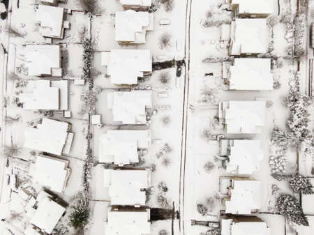 Aerial View from Above of a Residential Neighborhood with homes and trees covered in white after a big snow storm in the Lower Mainland. Taken in Coquitlam, Vancouver, BC, Canada.