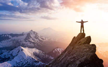 Adventure, Explore and Lifestyle Concept Composite. Adventurous Man Hiker With Hands Up on top of a Steep Rocky Cliff. Sunset or Sunrise. Landscape Taken from Washington, USA. Banque d'images