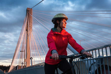 Caucasian Woman riding a Bicycle on a path at Port Mann Bridge during vibrant Sunset. Taken in Surrey, Vancouver, British Columbia, Canada. Foto de archivo