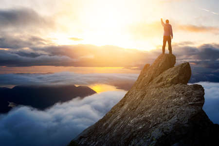 Adventurous Man Hiker With Hands Up on top of a Steep Rocky Cliff. Sunset or Sunrise. Landscape Taken from British Columbia, Canada. Concept: Adventure, Explore, Hike, Lifestyle. Composite.