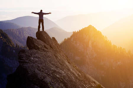 Adventurous Man Hiker With Hands Up on top of a Steep Rocky Cliff. Sunset or Sunrise. Composite. Landscape Taken from British Columbia, Canada. Concept: Adventure, Explore, Hike, Lifestyle Banque d'images