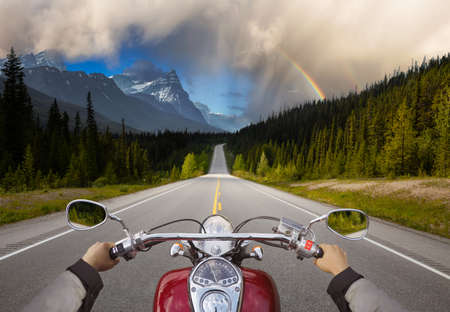 Biker Riding on a Motorcycle on a scenic Road in the Canadian Rockies. Image Composite. Background from Banff, Alberta, Canada. Archivio Fotografico
