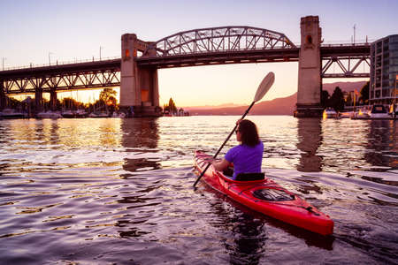 Girl Kayaking in a Modern City during a vibrant golden sunny sunset. Taken in False Creek, Downtown Vancouver, British Columbia, Canada. 版權商用圖片